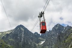 Red cable car with tourists in the Tatra mountains on the route Skalnate pleso - Lomnica peak. Royalty Free Stock Photos