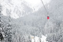 Red cable car in winter alpine landscape. Red cable car with mountains and fir forests covered by snow in background stock photography