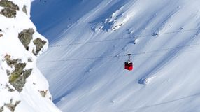 Red cable car in winter alpine landscape royalty free stock images