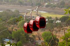 Red cable cars with black windows going down. Three red cable cars with black windows going down, with beautiful landscape in the background Royalty Free Stock Photography