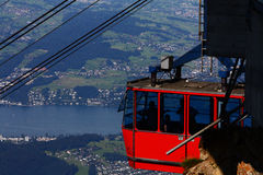 Red cableway car. High in the Alps with a lake below Royalty Free Stock Photo