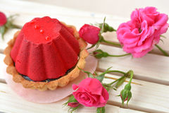 Red cake full of chocolate near pink rose on wooden texture. Red and sweet cake full of chocolate near pink rose on wooden texture close up Stock Photo