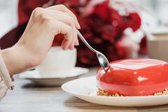 Red cake in the shape of a heart is on the table. Two hands with spoons, male and female, stretch into a pie. Romantic date, Valentine`s Day royalty free stock image