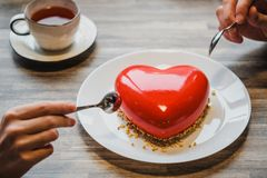 Red cake in the shape of a heart is on the table. Two hands with spoons, male and female, stretch into a pie. royalty free stock photos