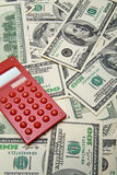 Red calculator on the $100 banknotes background Royalty Free Stock Photos