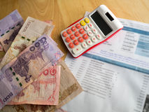 The red calculator and bank note is placed on a wooden table .After calculating the bill of payment Stock Image
