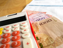 The red calculator is placed on a banknote.After calculating the bill of payment Stock Photo