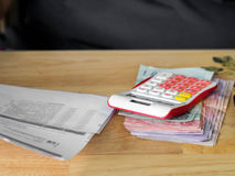 The red calculator is placed on a banknote.After calculating the bill of payment Royalty Free Stock Images