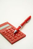 Red calculator and red pen Stock Photo