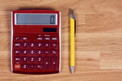 Red calculator and yellow pen on a wooden oak table Royalty Free Stock Images