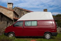 Red camper van parked on the grass in a rural setting stock photography