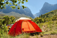 Red camping tent in misty mountains