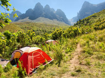 Red camping tent next to trail in mountains Royalty Free Stock Photos