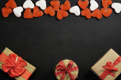 Red candies and gift boxes with copy space on black Royalty Free Stock Images
