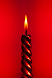 Red candle. Red burning candle on colourful vivid background Royalty Free Stock Photo