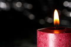 Red candle against black Stock Photos