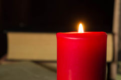 Red candle against several books Stock Images