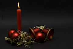 Red candle, balls and bells. Stock Photos