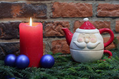 Red candle, blue christmas balls and Santa Claus teapot Stock Images