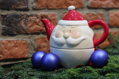 Red candle, blue christmas balls and Santa Claus teapot Royalty Free Stock Images