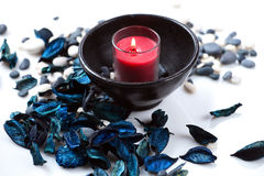 Red candle and a blue potpourri Stock Images