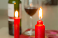 Red candle and a bottle of wine Stock Photo