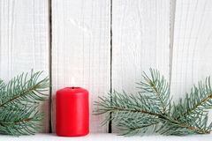 Red candle and branches of blue spruce Stock Image