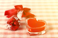 Red candle with candy and knot Stock Photography