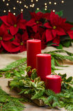 Red candle centerpiece with greens Stock Photography