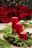Red candle centerpiece with greens and red balls. Red candle centerpiece with poinsetias and greens and red balls Royalty Free Stock Image