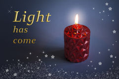 Red candle Christmas design. Red Christmas candle burning against a dark blue background, with the words Light has come in shiny gold text Royalty Free Stock Images