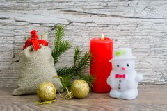 Red candle with christmas fir tree decorations. And gift bag and snowman Stock Photography