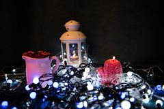 A red candle with Christmas lights in the atmospheric light Royalty Free Stock Images