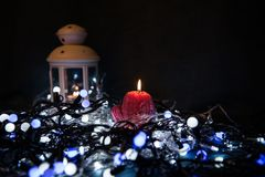 A red candle with Christmas lights in the atmospheric light Stock Photography
