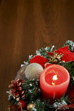 Red Candle Chtistmas Decoration. A red Christmas decoration sitting on a brown table. A red lighted candle is in the middle with red ribbons, green boughs and Stock Photography