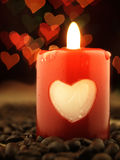 Red candle and coffee on the table. Shiny hearts in background. Stock Photos