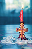 Red candle in cross candlestick with rock crystal beads Royalty Free Stock Photo