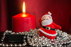 Red candle with a decor from silver balls and toy Santa Claus Stock Image