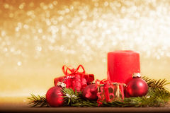 Red candle decorated for Christmas with baubles and gifts Royalty Free Stock Photography