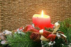 Red Candle Decoration with a Thatched Background. A lighted red candle with red ribbons and green boughs at its base celebrating Christmas Royalty Free Stock Photography