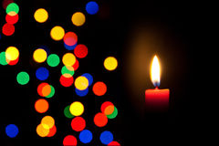 Red candle with defocused colorful lights Stock Photo