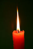 Red candle fire. Lone red candle shining brightly Stock Photo