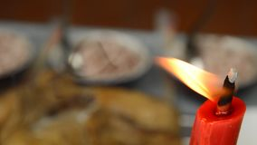 Red candle fire with blur food background for offering ancestor in Chinese spirits day. Panning of red candle fire with blur food background for offering stock video footage