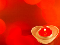 Red candle with fire on red background Stock Photo
