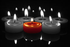 Red candle with flame on black and white. Glowing flames from centre red candle with reflections top and bottom Royalty Free Stock Photography