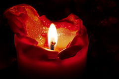Red candle with flame and melting wax against a dark background Stock Images