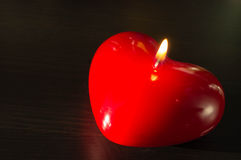 Red candle in the form of heart Stock Photos