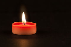 Red candle glowing in the dark Royalty Free Stock Image