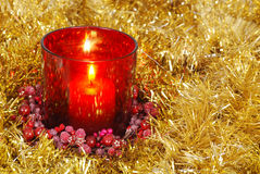 Red candle in gold garland Royalty Free Stock Image