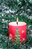 Red candle and green tinsel Stock Photos